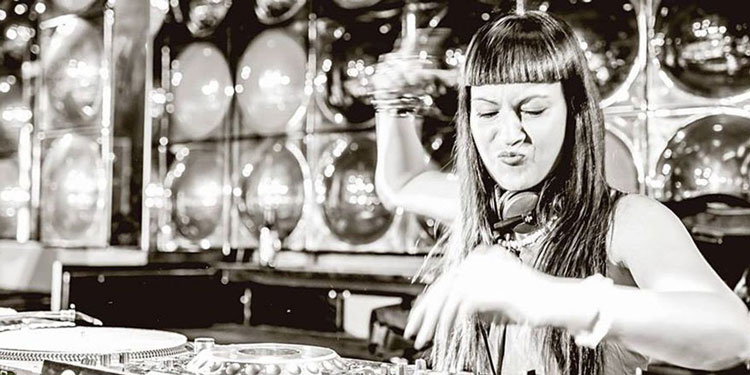 Black and white photo of Dj Fatima Hajji playing hard tech dance music. She is using Pioneer DJ equipment.