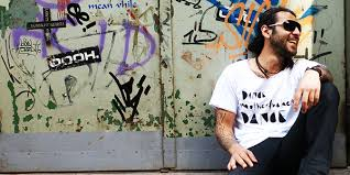 DJ Sis sitting against wall with graffiti on it, wearing jean, a white t-shirt and sunglasses.