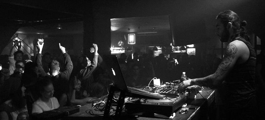A black and white image of DJ Sis behind some DJ equipment, performing to people in a club, who are dancing with their hands in the air.