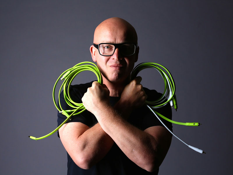 Stephan Bodzin looking directly into the camera while holding studio equipment leads
