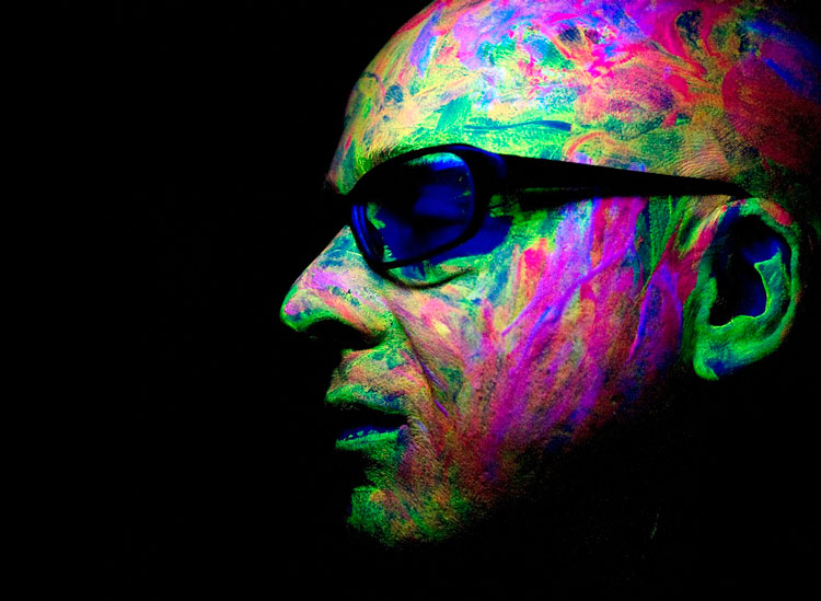 An image of Stephan Bodzin's head covered with multi coloured face paint and looking to the left.