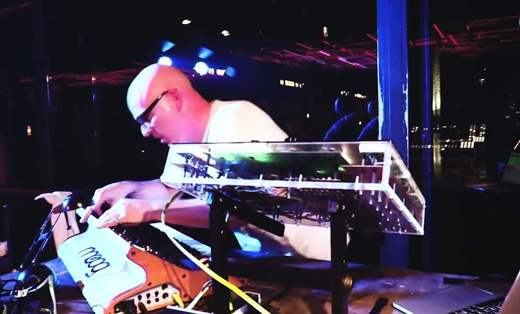 Stephan Bodzin looking down at and using a Moog keyboard while performing a live set in Berlin