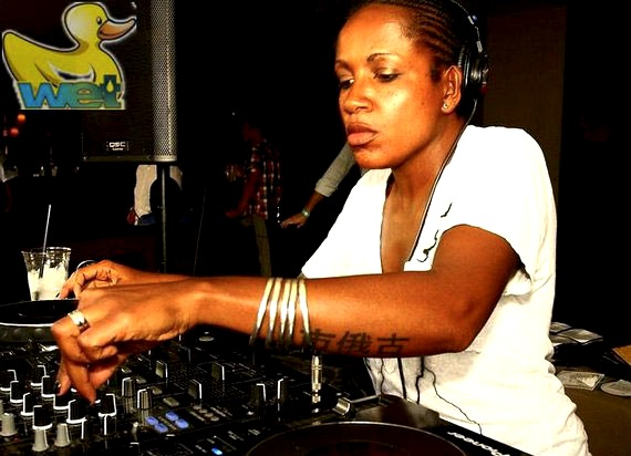 DJ Heather wearing a white t-shirt and headphones, using a pioneer mixing set up, during one of her DJ sets.
