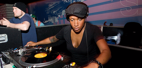 DJ Heather using pioneer turntables while mixing a vinyl record with a yellow label. She is wearing a black t-shirt and a black cap with her headphones on one ear.